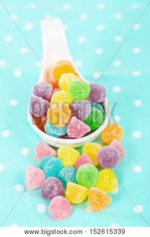 Colorful jelly candies in white spoon on tablecloth.