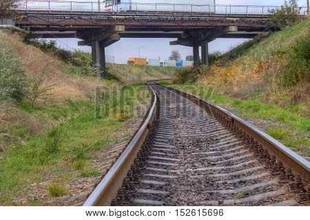 railway track with bridge above old ukrainian railways. wagon cargo trucks are on background