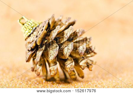 Gold pine cones for christmas on abstract golden background