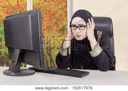 Arabian businesswoman sitting in front of computer while holds head and looks stress with autumn background on the window