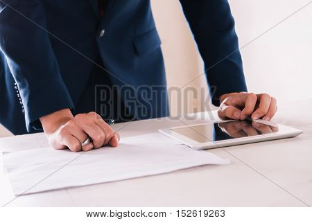 Business Man Writing On Business Documents And Using Tablet On The Work Desk