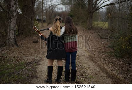 Two young girls look back at house from driveway.