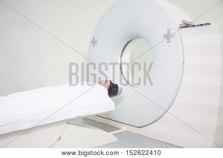 A sophisticated MRI Scanner at hospital with woman patient.