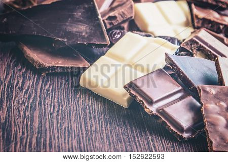 Close up of a heap of various chocolate pieces over dark wood background. Dark milk white and nuts chocolate bars. Copy space. Vintage effect.