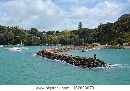 Auckland New Zealand - October 04 2016: Man and boy fishing from the Breakwater at Waiheke Island Auckland.