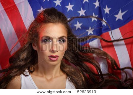 Young attractive girl on the background of the US flag. She a T-shirt. Long curly hair. Portrait of a real patriot.