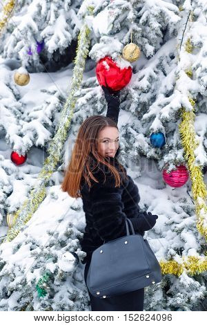 Portrait of pretty attractive girl in fur coat and gloves in the winter park. She decorates the Christmas tree toys. Winter fun. Walks in the open air. Christmas mood.