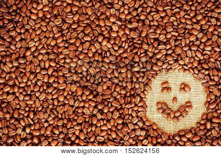 Face coffee frame made of coffee beans on burlap texture.