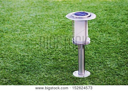 Solar-powered lamp on green grass background. Selective focus.