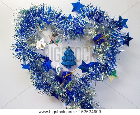 Christmas ornament in silver and blue on white background. New Year decoration flat lay. Shining and sparkling ribbon in heart shape with small presents and fir tree inside. Blue glitter firtree