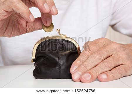 Old senior hands holding coin and small retro styled money pouch