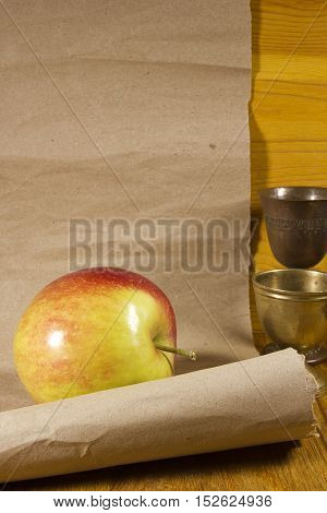 Apple and a roll of paper on a wooden background