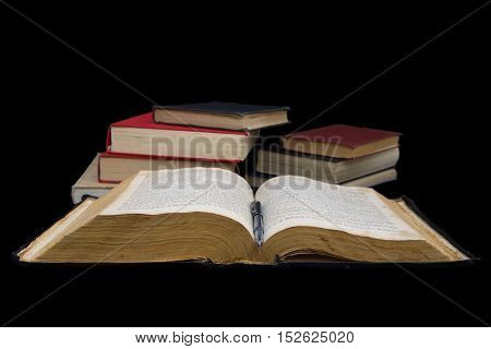 Opened Bible and other books isolated on a black background.