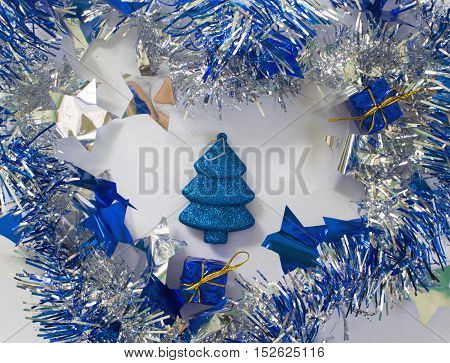 Christmas ornament in silver and blue on white background. New Year decoration flat lay. Shining and sparkling ribbon with fir tree toy inside. Blue glitter firtree. New Year or Christmas composition