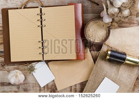 Diary for records and garlic on old wooden background
