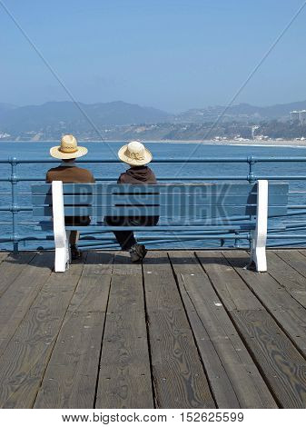 Sitting on a bench, a couple looks the Atlantic Ocean and Santa Barbara beach in front of them. Photo taken early morning in May. Daylight / Couple looking at the Santa Barbara beach / Santa Monica, California, USA.