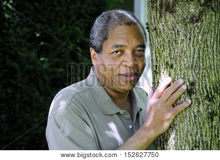 African american male standing by a tree outdoors.