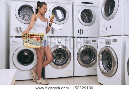 Girl texting when waiting in laundry room
