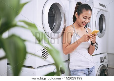 Portrait of cheerful girl in laundromat text messaging