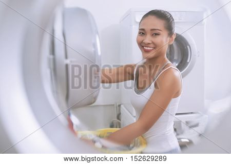 Smiling Asian woman loading dirty laundry in washing machine