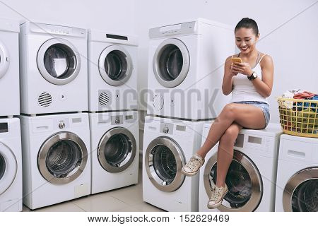 Vietnamese young girl sitting on washing machine and texting