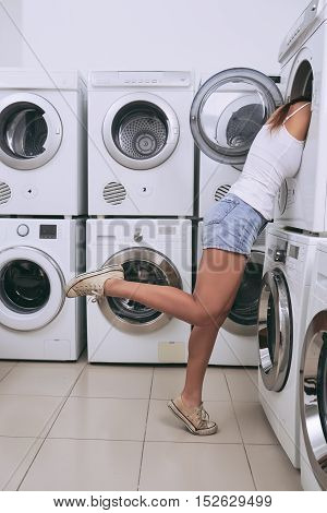 Side view of young woman looking into washing machine