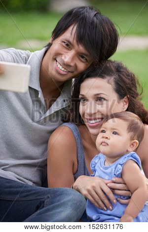 Portrait of smiling family taking selfie outdoors