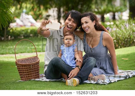 Cheerful family taking photos when having picnic in the park