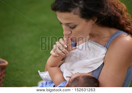 Young mother hissing hand of her little baby