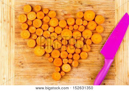 Chopped Carrots As Heart Shape Beside Knife