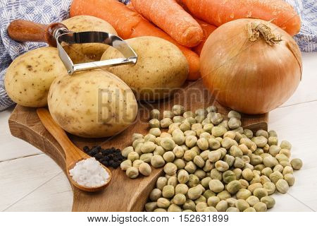 ingredients such as carrots potatoes onions black peppercorns coarse salt and dried peas to cook a vegetarian pea soup
