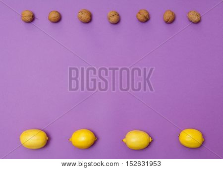 Nuts and lemons in rows on purple background with copy space