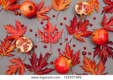 Pomegranates and autumn red fallen leaves pattern on grey background