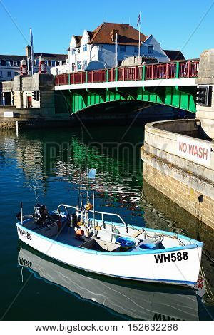 WEYMOUTH, UNITED KINGDOM - JULY 18, 2016 - View of the twin leaf bascule bridge in the harbour with a small boat in the foreground Weymouth Dorset England UK Western Europe, July 18, 2016.