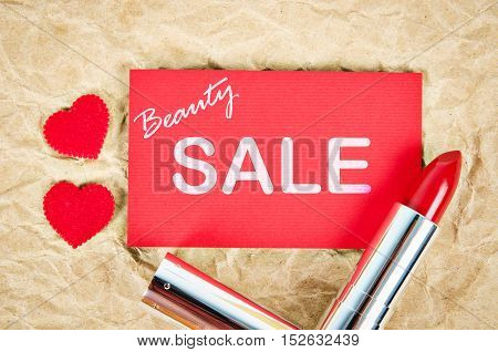 Beauty sale card with red lipstick on brown paper.