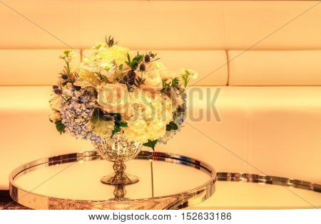 Wedding bouquet in a silver vase on a mirror table with white chairs and a sofa in the background. Flowers include white poppy Papaver species, white roses, blue thistle flowers, hydrangea and sweat pea.