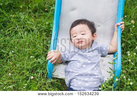 Little Asian Kid Playing Slide At The Playground, Accident