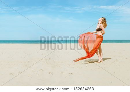 pretty woman on beach wearing silk fabric sarong