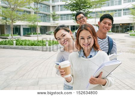 Four cheerful Vietnamese college students on campus
