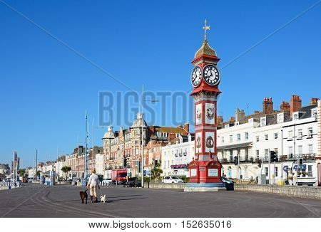 WEYMOUTH, UNITED KINGDOM - JULY 19, 2016 - View of Queen Victorias Jubilee clock tower along the Esplanade promenade with hotels and guesthouses to the rear Weymouth Dorset England UK Western Europe, July 19, 2016.