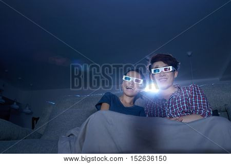 Young couple enjoying home cinema in dark room