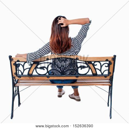 Back view of a woman sitting on a bench.  girl  watching. Rear view people collection.  backside view of person.  Isolated over white background. Brunette sitting on the bench arm straightens hair.