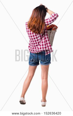 Back view of woman with  basket of dirty laundry. girl is engaged in washing.   Isolated over white background. Girl in shorts holding a laundry basket and the second arm straightens hair.