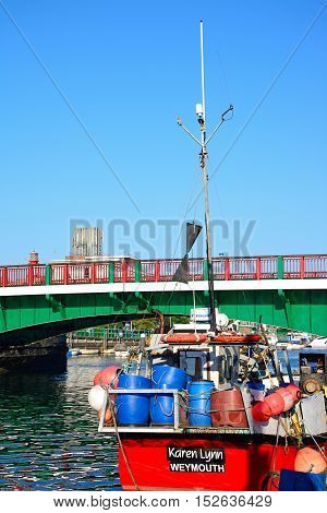 WEYMOUTH, UNITED KINGDOM - JULY 19, 2016 - View of the twin leaf bascule bridge and with a fishing boat in the foreground Weymouth Dorset England UK Western Europe, July 19, 2016.