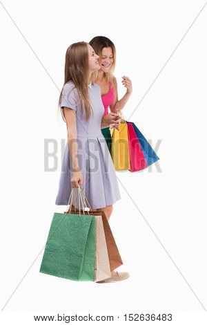 side view of  two walking women  with shopping bags. backside view of person.  Rear view people collection. Isolated over white background. Two girls walk with shopping bags in their hands.