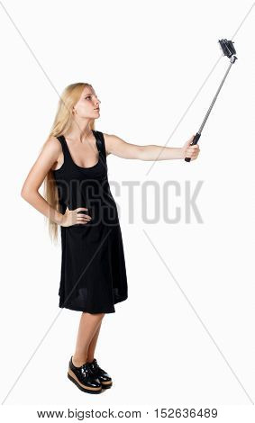 back view of standing young beautiful  girl with tablet computer in the hands of. girl  watching. Isolated over white background. The girl with a leather backpack poses for a selfie.