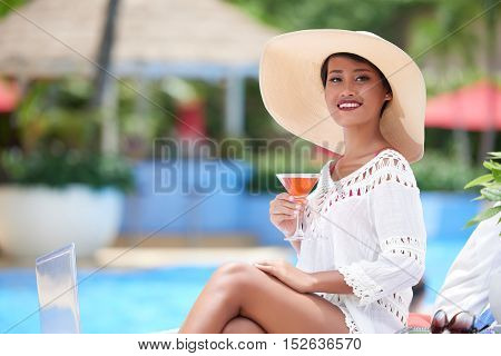 Beautiful Asian woman enjoying fresh cocktail by pool