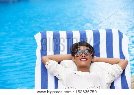 Smiling woman in sunglasses relaxing in chaise-lounge