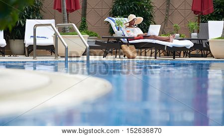 Beautiful woman enjoying working on laptop by swimming pool