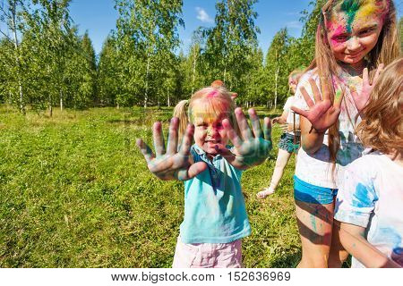 Portrait of happy cute little girl on color festival with covered palms and face
